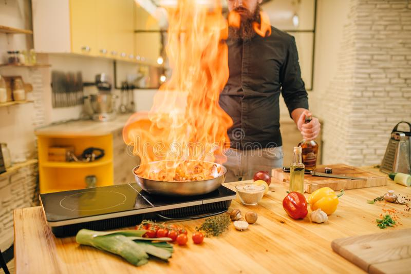 Männlicher Chef, der Fleisch mit vetables auf Feuer kocht lizenzfreie stockbilder