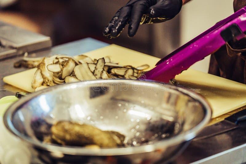 Männlicher Chef Slicing Pickled Cucumbers für Salate, Heiratsmahlzeit lizenzfreie stockfotos
