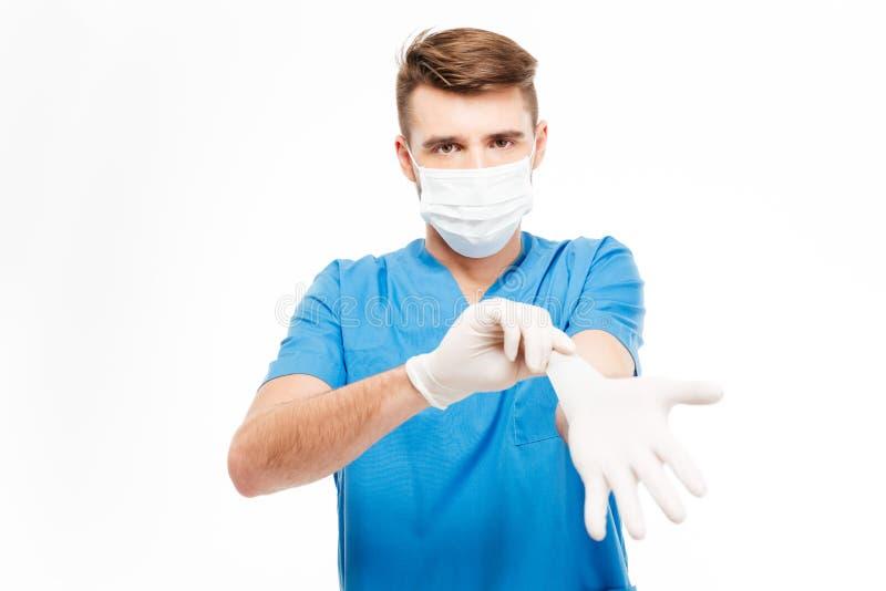 Männlicher Chirurg, der auf Handschuhe sich setzt lizenzfreies stockbild
