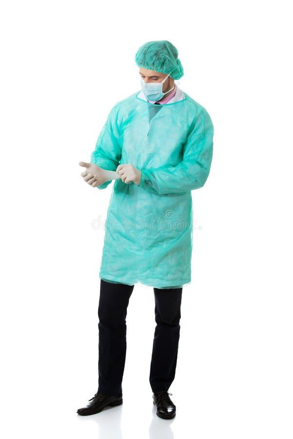 Männlicher Chirurg, der auf Schutzhandschuhe sich setzt lizenzfreies stockbild