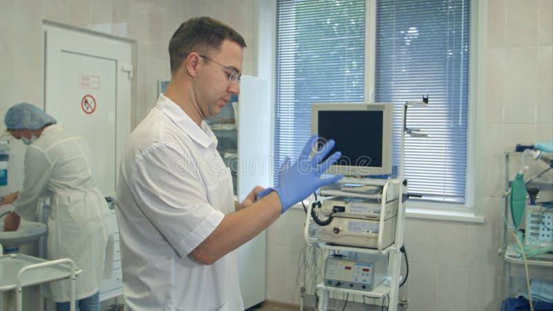 Männlicher Chirurg, der auf sterile Gummihandschuhe für Chirurgie während Krankenschwester wäscht ihre Hände in einen Chirurgiera lizenzfreie stockfotos