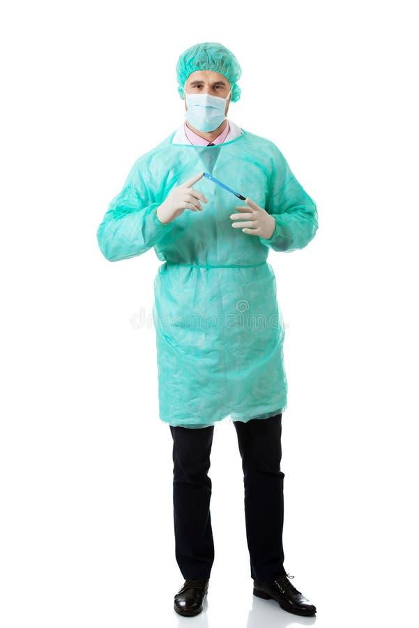 Männlicher Chirurg mit einem Skalpell stockfotografie