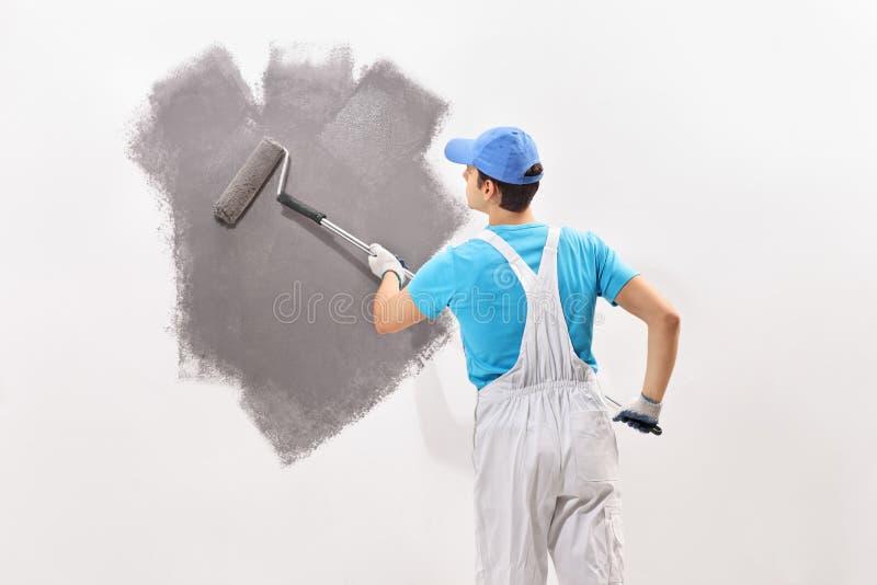 Männlicher Dekorateur, der eine Wand mit grauer Farbe malt stockbild