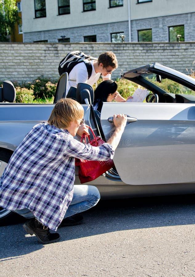 Männlicher Dieb, der Handtasche vom Auto stiehlt lizenzfreies stockbild