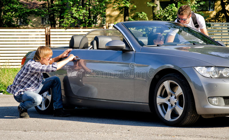 Männlicher Dieb, der zum steat etwas vom Auto versucht stockfotos