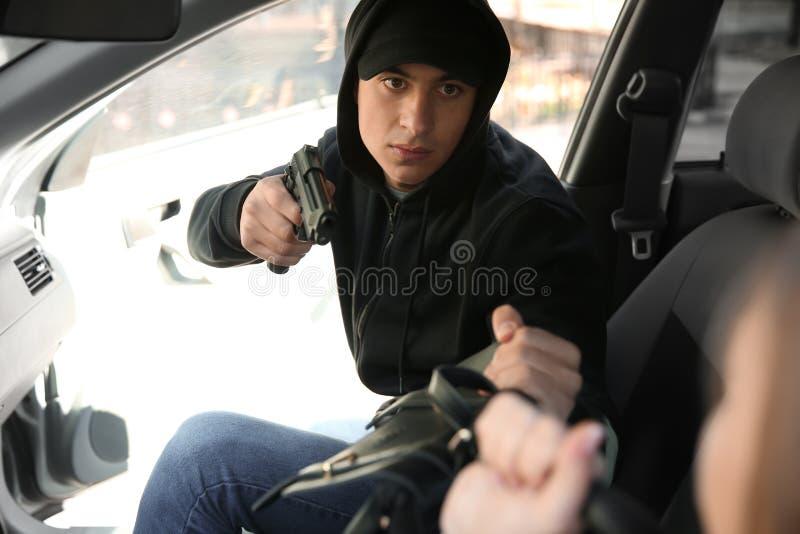 Männlicher Dieb mit Gewehr Tasche vom Autofahrer stehlend stockbilder
