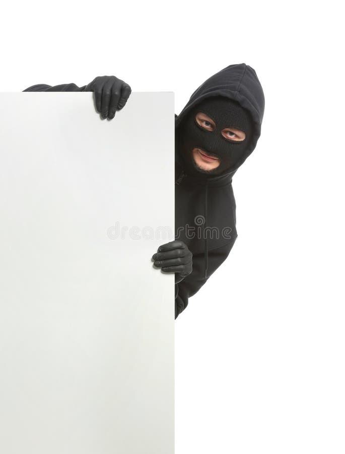 Männlicher Dieb mit leerem Plakat auf weißem Hintergrund stockbild