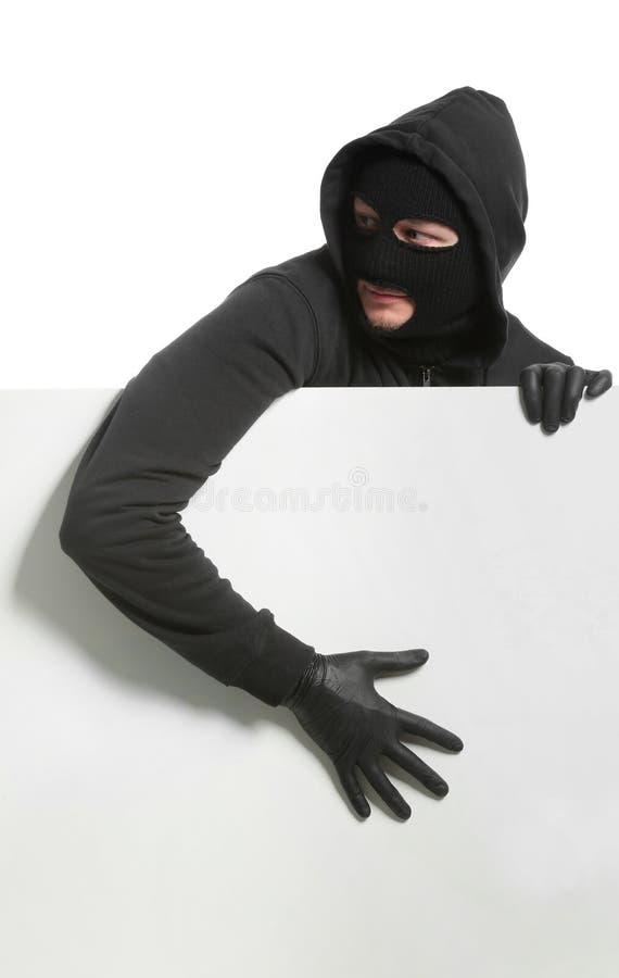 Männlicher Dieb mit leerem Plakat auf weißem Hintergrund stockfotografie