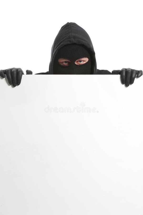 Männlicher Dieb mit leerem Plakat auf weißem Hintergrund stockfotos