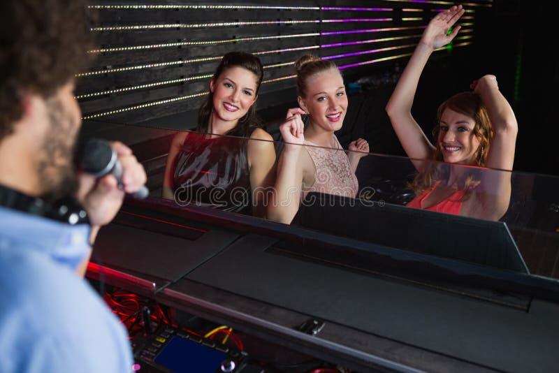 Männlicher Diskjockey, der Musik mit drei Frauen tanzen auf den Tanzboden spielt lizenzfreie stockfotos