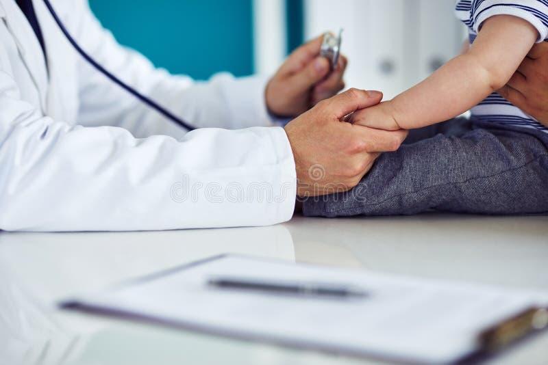 Männlicher Doktor überprüft ein Kind in einer Klinik lizenzfreies stockbild