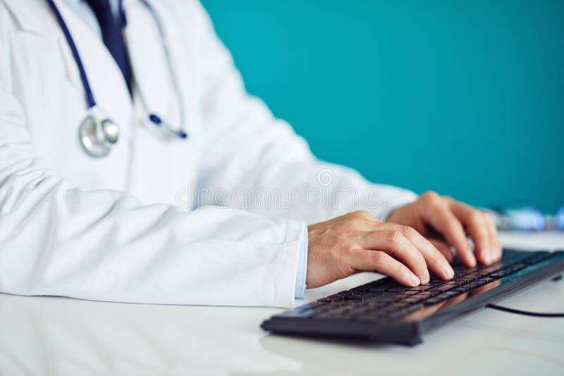 Männlicher Doktor arbeitet mit Computer stockbild