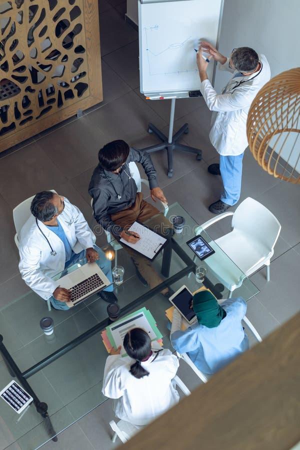 Männlicher Doktor, der über Flip-Chart beim Treffen am Krankenhaus erklärt lizenzfreie stockfotografie