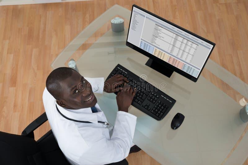 Männlicher Doktor, der auf Computertastatur schreibt lizenzfreie stockfotografie