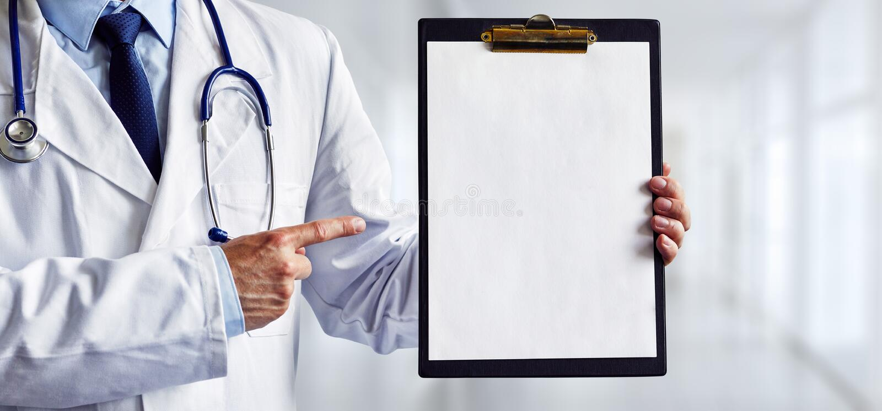 Männlicher Doktor, der auf ein leeres medizinisches Klemmbrett zeigt lizenzfreie stockfotos