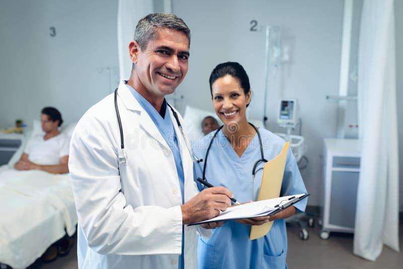 Männlicher Doktor, der auf Klemmbrett in den Bezirk am Krankenhaus schreibt stockfotos