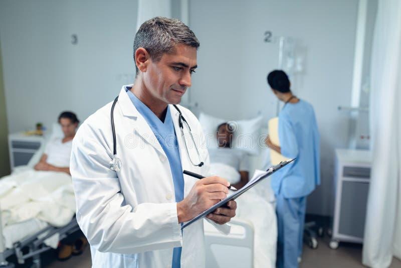 Männlicher Doktor, der auf Klemmbrett in den Bezirk am Krankenhaus schreibt lizenzfreie stockfotografie