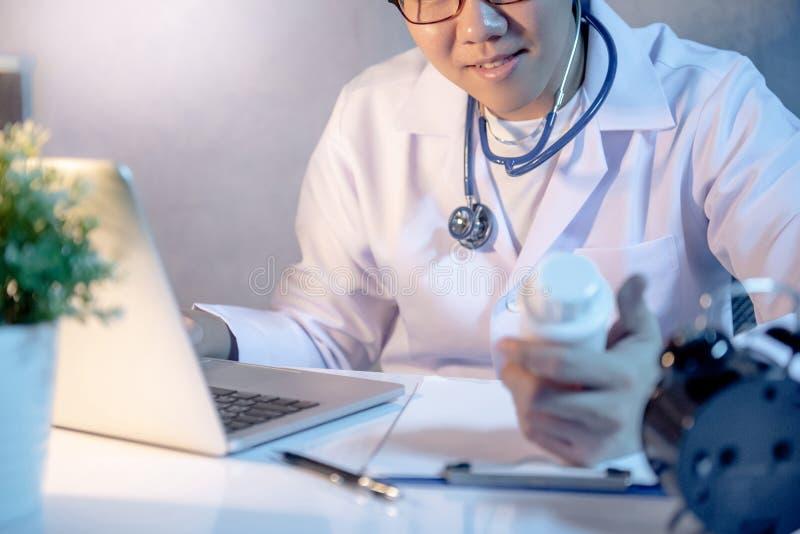Männlicher Doktor, der das Tablettenfläschchen arbeitet im Krankenhaus betrachtet lizenzfreie stockfotografie