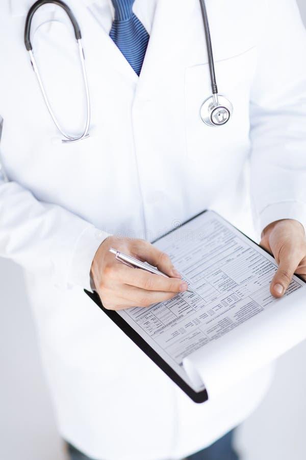 Männlicher Doktor, der in der Hand Verordnungspapier hält stockfotos