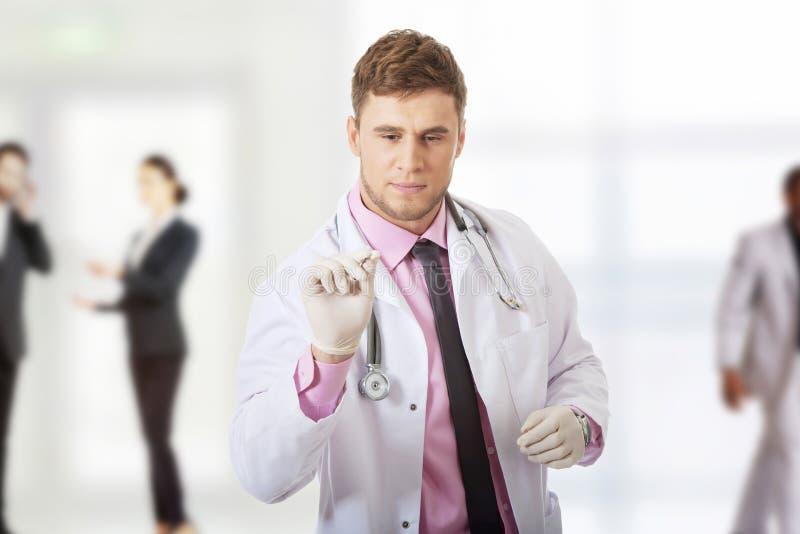 Männlicher Doktor, der eine Spritze anhält stockfotos