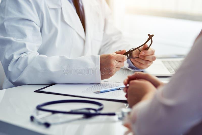 Männlicher Doktor, der an einem Tisch sitzt und mit seinem Patienten sich berät stockfotografie