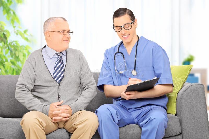 Männlicher Doktor, der mit einem älteren Patienten spricht lizenzfreies stockbild