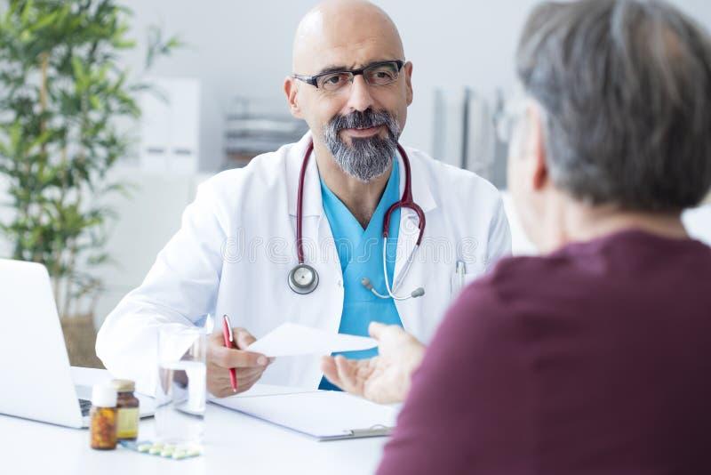 Männlicher Doktor, der mit Patienten spricht lizenzfreies stockfoto