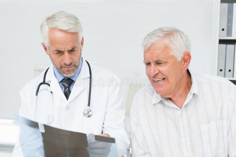 Männlicher Doktor, der Röntgenstrahlbericht älterem Patienten erklärt stockbild