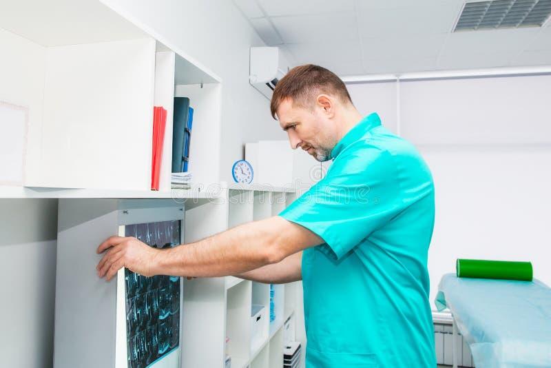Männlicher Doktor, der Röntgenstrahlbild des zervikalen Dorns in seinem Büro betrachtet Osteopathy, Chiropraktik, Physiotherapie  stockbild