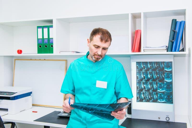 Männlicher Doktor, der Röntgenstrahlbild des zervikalen Dorns in seinem Büro betrachtet Osteopathy, Chiropraktik, Physiotherapie  stockbilder