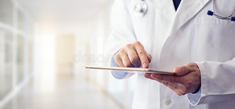 Männlicher Doktor, der seine digitale Tablette verwendet stockbilder