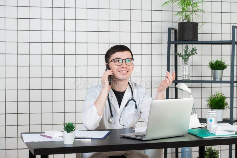 Männlicher Doktor, der Telefon beim an Computer bei Tisch arbeiten in der Klinik verwendet lizenzfreie stockfotografie