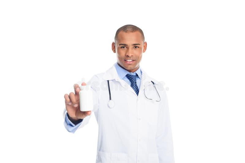 männlicher Doktor des Afroamerikaners im weißen Mantel mit Tablettenfläschchen, stockfoto
