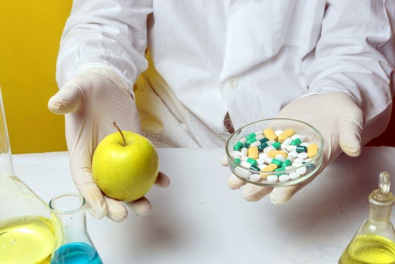 Männlicher Doktor gekleidet im weißen Mantel, Diätpillen gehalten von Doktormann und Äpfel in der anderen Hand als empfehlende Me lizenzfreie stockfotos