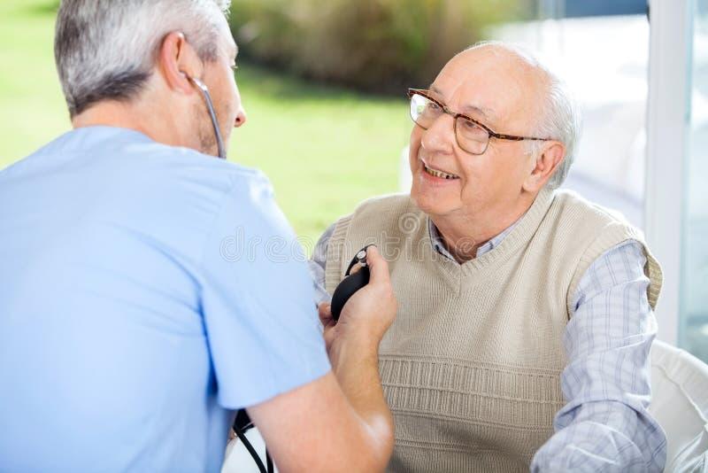 Männlicher Doktor Measuring Blood Pressure des älteren Mannes lizenzfreie stockbilder