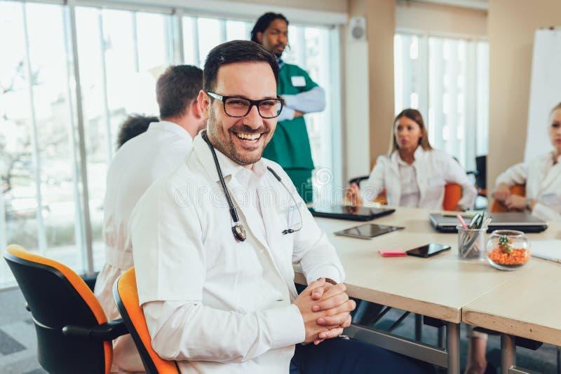 Männlicher Doktor mit Kollegen im Hintergrund, Doktor, der Kamera betrachtet lizenzfreie stockfotografie
