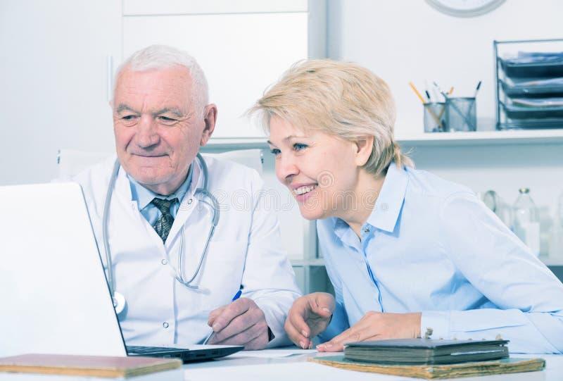 Männlicher Doktor mit weiblichem Kunden lizenzfreie stockfotografie