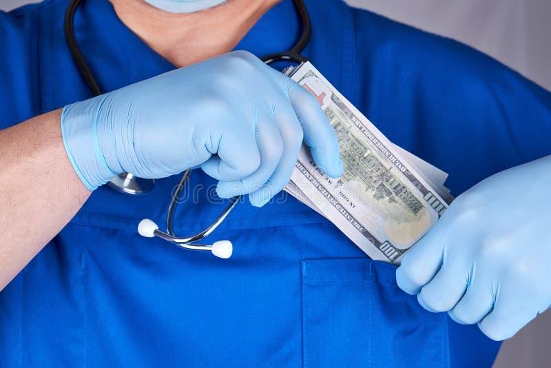 Männlicher Doktor setzt ein Pack von Dollar in seine Hemdtasche, Konzept des Nehmens von Bestechungsgeldern ein stockbild