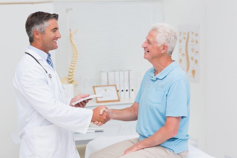 Männlicher Doktor und älterer Patient, die Hände rüttelt lizenzfreie stockbilder