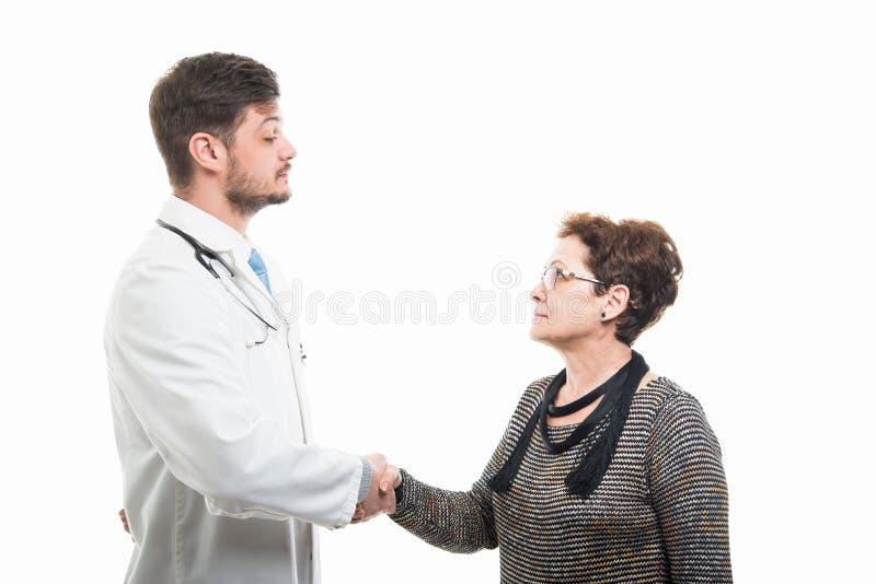 Männlicher Doktor und weiblicher älterer Patient, die Hände rüttelt lizenzfreie stockfotos