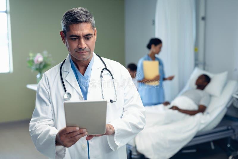Männlicher Doktor unter Verwendung der digitalen Tablette im Bezirk am Krankenhaus stockfotos