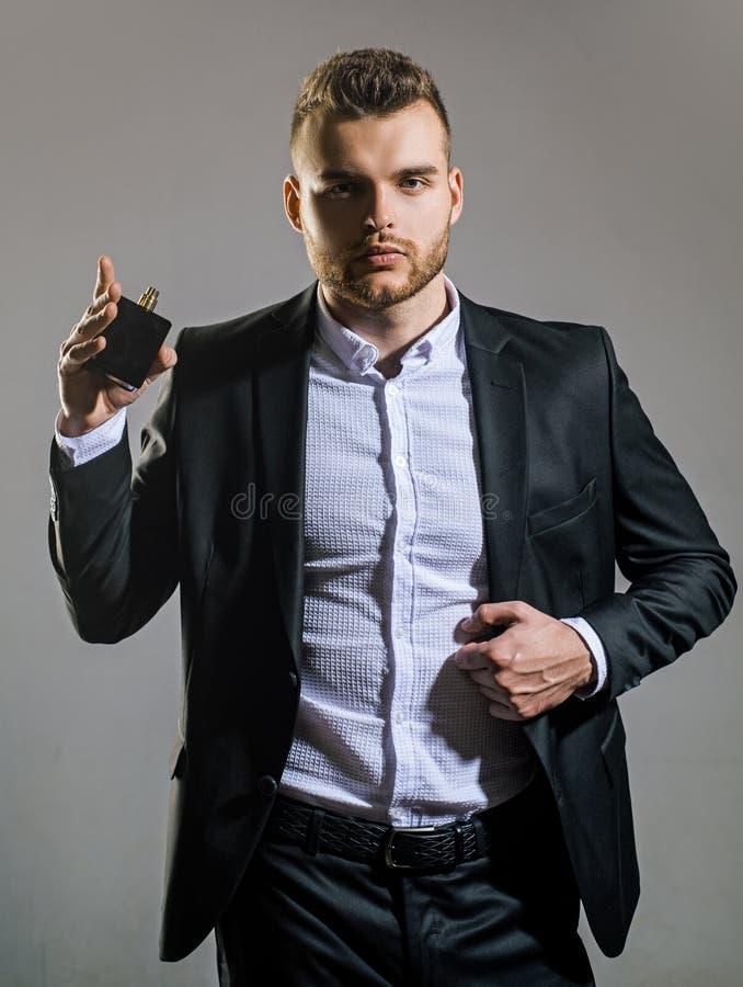 Männlicher Duft und Parfümerie, Kosmetik Mann, der Flasche der Parfümerie hält Flasche und Wasser lizenzfreie stockbilder