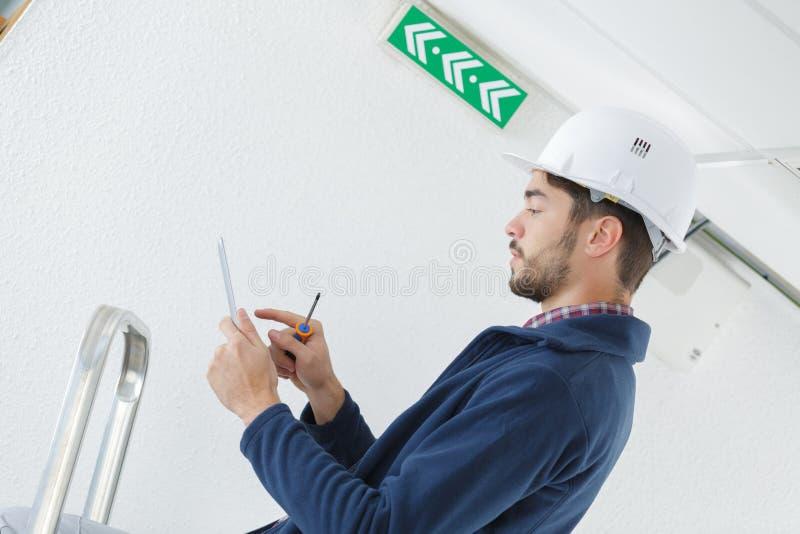 Männlicher Elektriker, der auf dem Stehleiter repariert Licht steht lizenzfreie stockbilder