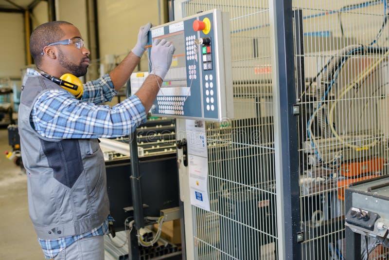 Männlicher Elektriker, der industrielle Maschinensteuerkomponente repariert stockfotografie