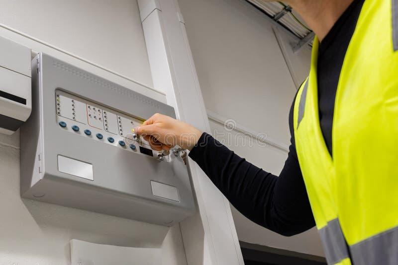 Männlicher Elektriker Opening Fire Panel im Server-Raum stockfotos