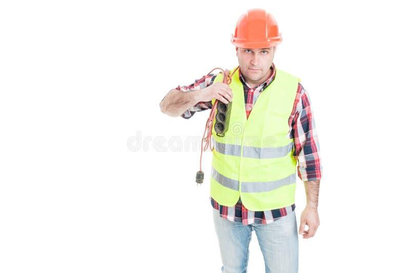 Männlicher Elektrikererbauer, der Verlängerungskabel auf Schulter hält stockbilder