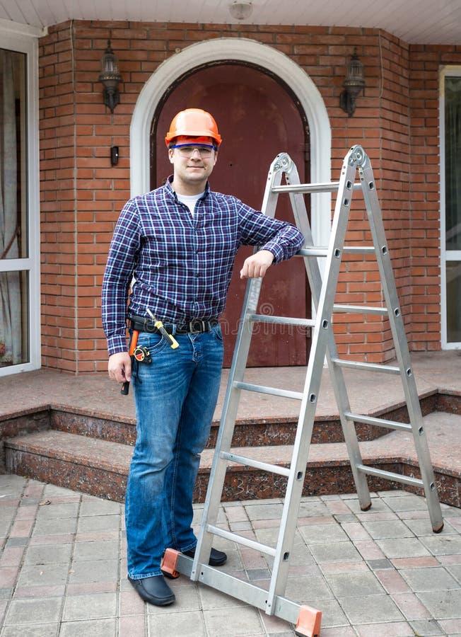 Männlicher Erbauer im Sturzhelm, der mit Leiter gegen Hauseingang aufwirft stockbild