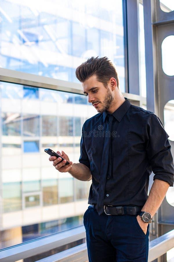 Männlicher erfahrener Manager unter Verwendung der Programme über das Mobiltelefon, stehend in der großen Firma lizenzfreies stockbild