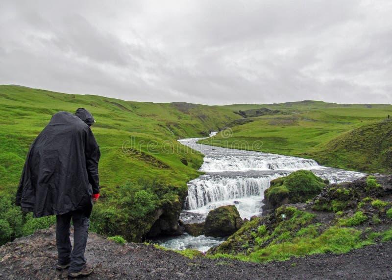 Männlicher erwachsener Wandererabenteurer, der im Regenmantel zurück steht im Freien wandert, Wasserfall in Laugaveur-Wanderung a stockfotografie