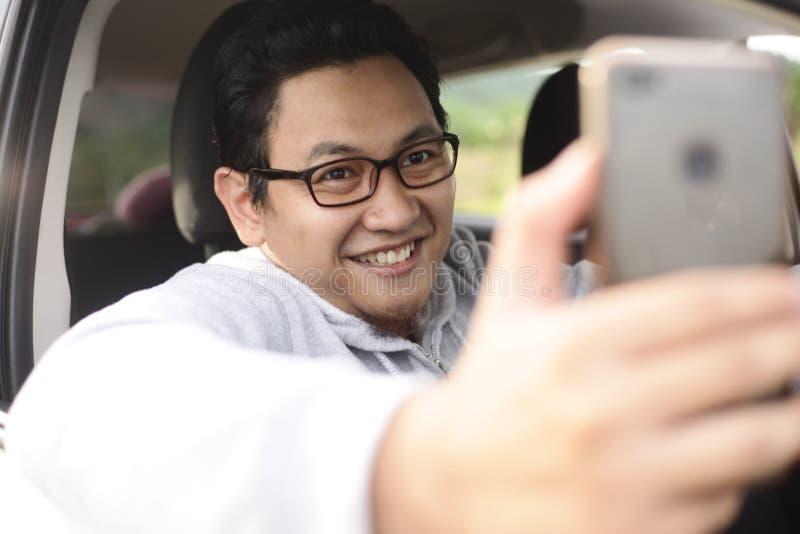 Männlicher Fahrer Taking Selfie Foto mit seinem intelligenten Telefon im Auto stockfotos